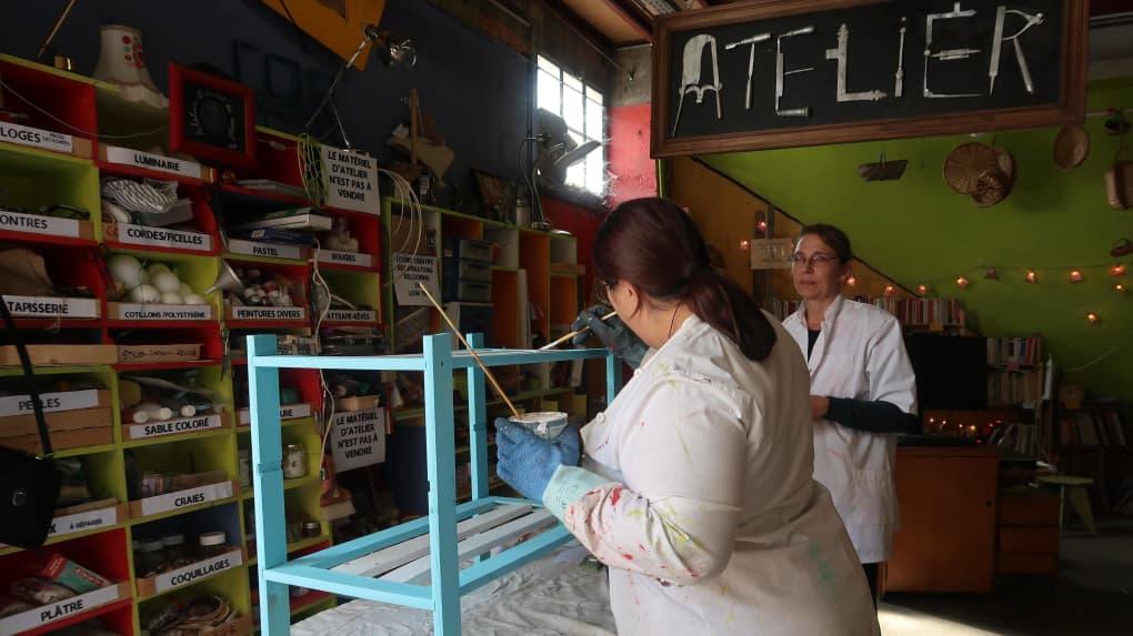 Deux bénévoles repeignent une étagère